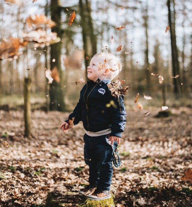 child playing with leaves in the woods